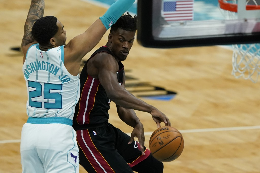 Miami Heat forward Jimmy Butler, right, passes around Charlotte Hornets forward P.J. Washington during the first half of an NBA basketball game on Sun...