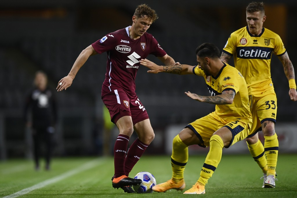 Torino's Mergim Vojvoda, left, in action during the Italian Serie A soccer match between Torino and Parma at the Olimpico Grande Torino stadium in Tur...