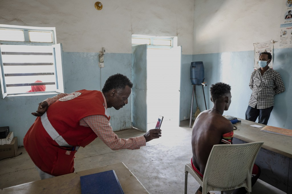 Surgeon and doctor-turned-refugee, Dr. Tewodros Tefera, uses his mobile phone camera to document the welts on the back from a beating by Eritrean sold...