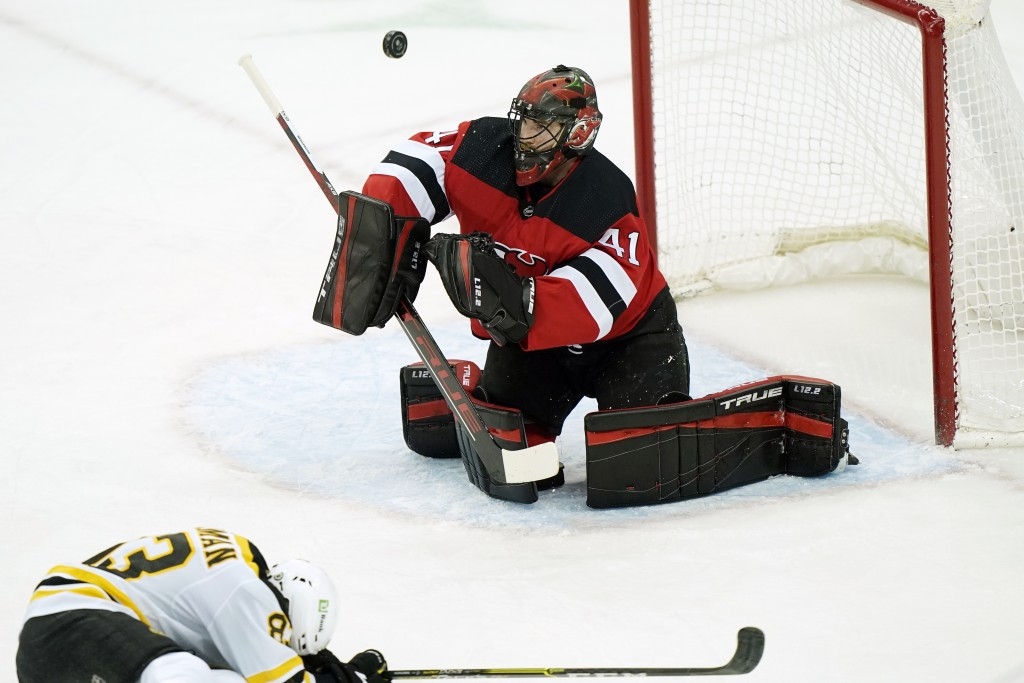 Boston Bruins center Karson Kuhlman (83) ducks as New Jersey Devils goaltender Scott Wedgewood (41) makes a save during the first period of an NHL hoc...