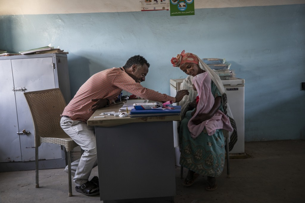 Dr. Tewodros Tefera treats a patient at the Sudanese Red Crescent Clinic in Hamdayet, Sudan, on March 17, 2021. (AP Photo/Nariman El-Mofty)