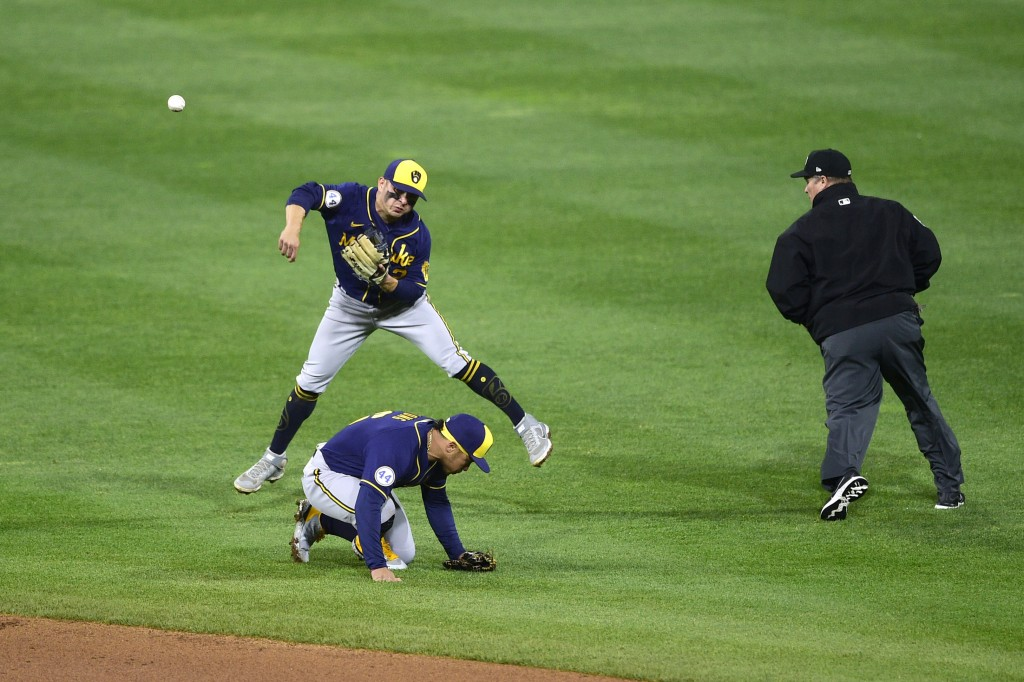 Milwaukee Brewers' Luis Urias throws to first base but is unable to make an out on an infield hit by Philadelphia Phillies' Odubel Herrera as Kolten W...