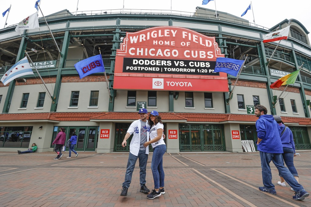 CORRECTS YEAR TO 2021-Los Angeles Dodgers fans Carlos Cativo and Nicole Ramos pose for a picture outside the Wrigley Field as a baseball game between ...