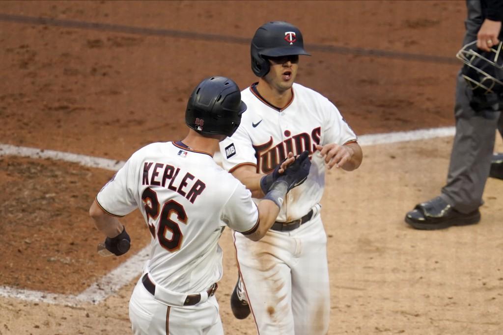 Minnesota Twins' Max Kepler, left, congratulates Alex Kirilloff after Kirilloff scored on a throwing error by Texas Rangers right fielder Joey Gallo i...