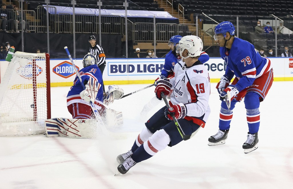 Nicklas Backstrom, center, of the Washington Capitals scores in the third period against Igor Shesterkin, left, of the New York Rangers during an NHL ...