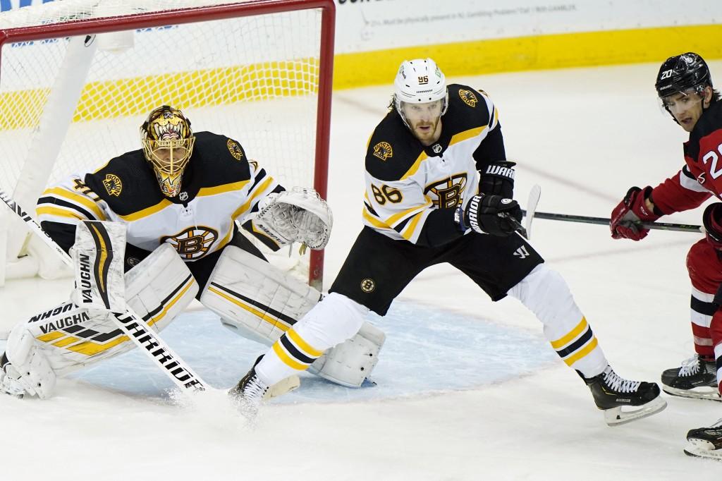 Boston Bruins defenseman Kevan Miller (86) defends the crease along with Boston Bruins goaltender Tuukka Rask (40) as New Jersey Devils center Michael...