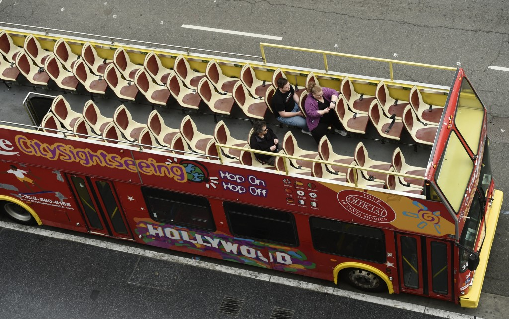 FILE - In this March 12, 2020, file photo, tourists sit in a mostly empty sightseeing bus on Hollywood Boulevard in the Hollywood section of Los Angel...