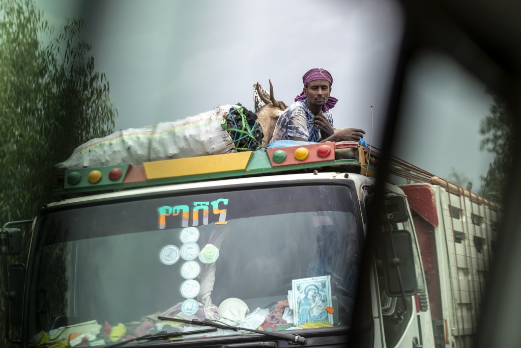 A man rides with goats and charcoal on the roof of a truck, seen through the window of a vehicle, near Danshe, a town in an area of western Tigray ann...