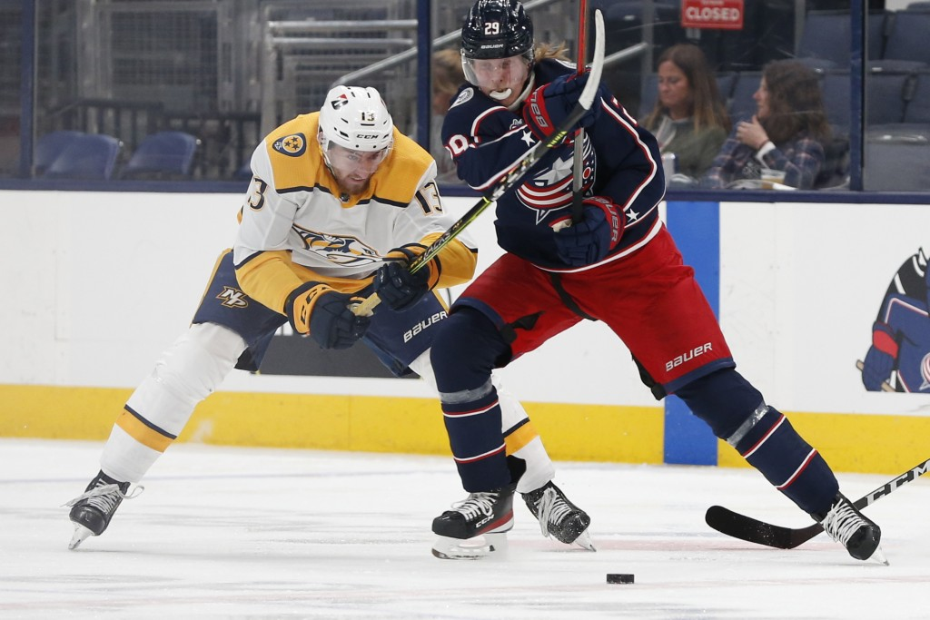 Nashville Predators' Yakov Trenin, left, and Columbus Blue Jackets' Patrik Laine chase the puck during the second period of an NHL hockey game Monday,...