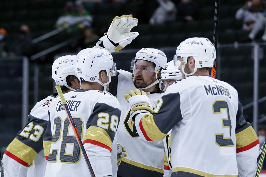 Vegas Golden Knights right wing Mark Stone (61), center, is congratulated by teammates after scoring against the Minnesota Wild in the second period d...
