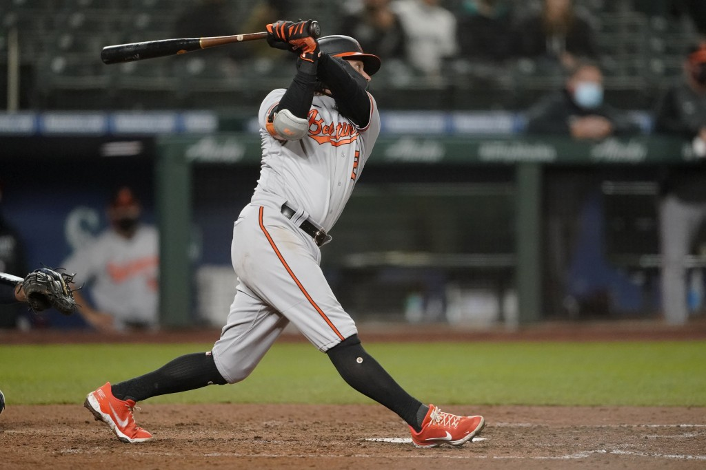 Baltimore Orioles' Freddy Galvis follows through on a two-run home run during the eigth inning of a baseball game against the Seattle Mariners, Monday...