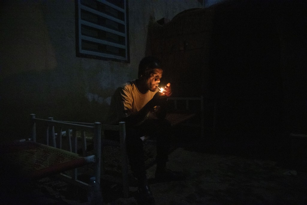 Surgeon and doctor-turned-refugee, Dr. Tewodros Tefera, lights a cigarette and rests on his bed after finishing his work, at the Sudanese Red Crescent...