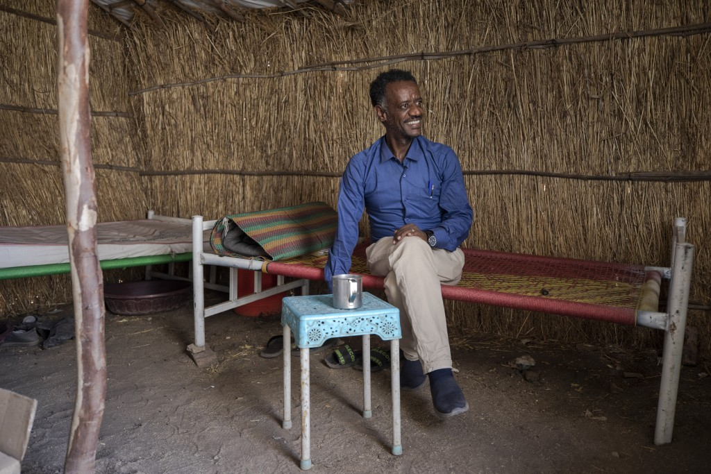 Surgeon and doctor-turned-refugee, Dr. Tewodros Tefera, takes a cigarette break inside his shelter at the Sudanese Red Crescent clinic where he works,...