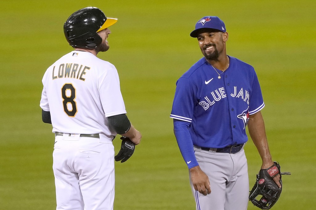 Toronto Blue Jays shortstop Marcus Semien, right, smiles at Oakland Athletics' Jed Lowrie (8) after Lowrie hit a double during the sixth inning of a b...