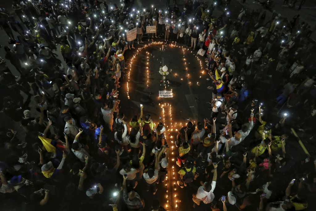 People light candles during a vigil in honor of Nicolas Guerrero who died after being shot during a national strike against tax reform in Cali, Colomb...