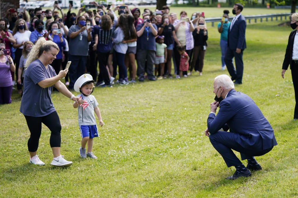 President Joe Biden stops outside at York High School and is greeted by a child and his mother, Monday, May 3, 2021, in Yorktown, Va. (AP Photo/Evan V...