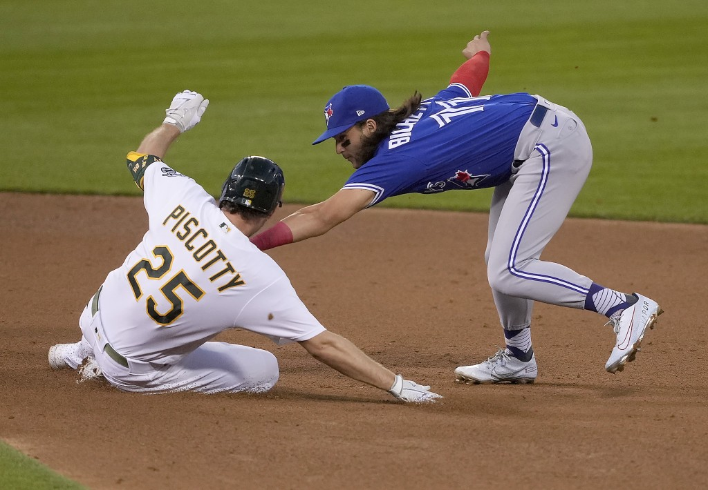 Toronto Blue Jays shortstop Bo Bichette, right, tags out Oakland Athletics' Stephen Piscotty, left, during the fourth inning of a baseball game in Oak...