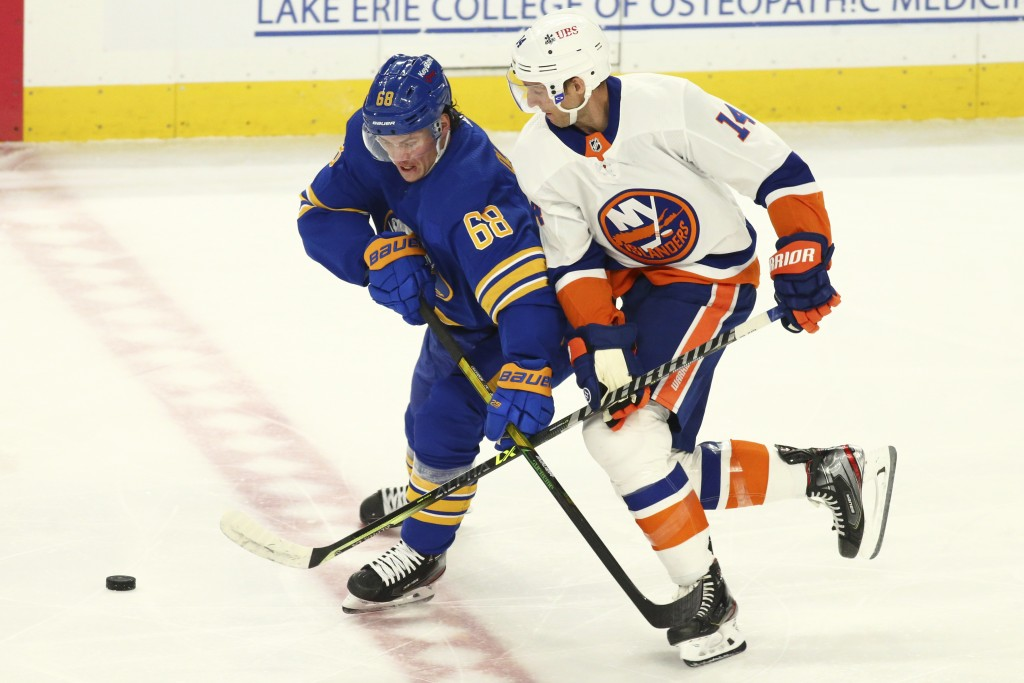 Buffalo Sabres forward Victor Olofsson (68) and New York Islanders forward Travis Zajac (14) battle for the puck during the first period of an NHL hoc...