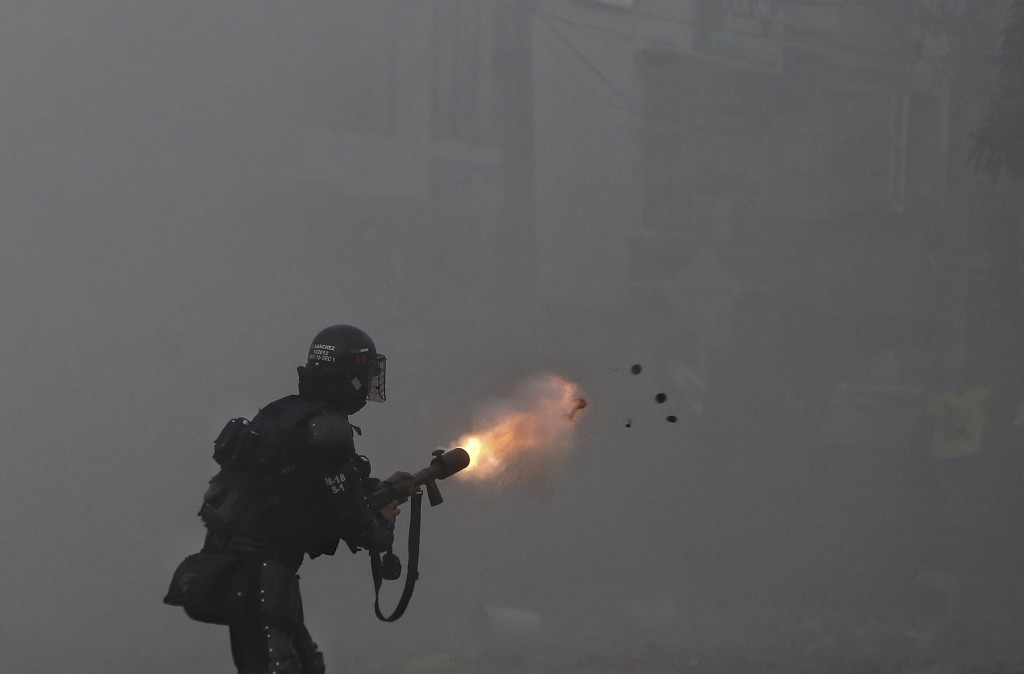 A police officer fires tear gas at protesters during a strike against tax reform in Cali, Colombia, Monday, May 3, 2021. Colombia's President Ivan Duq...