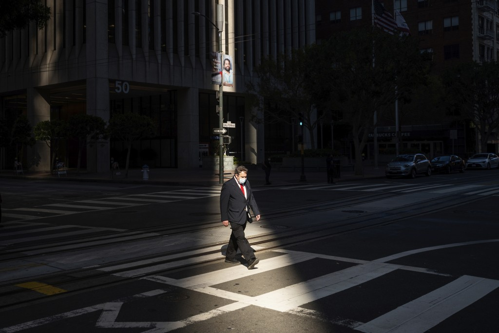 FILE - In this Oct. 21, 2020, file photo, a person crosses an intersection in San Francisco's financial district mid-afternoon, during what would've b...