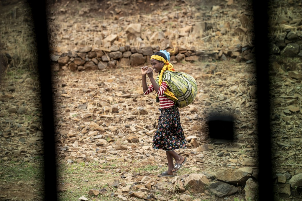 A girl walks by the side of the road, seen through a partially-open window of a vehicle, between Gondar and Danshe, a town in an area of western Tigra...