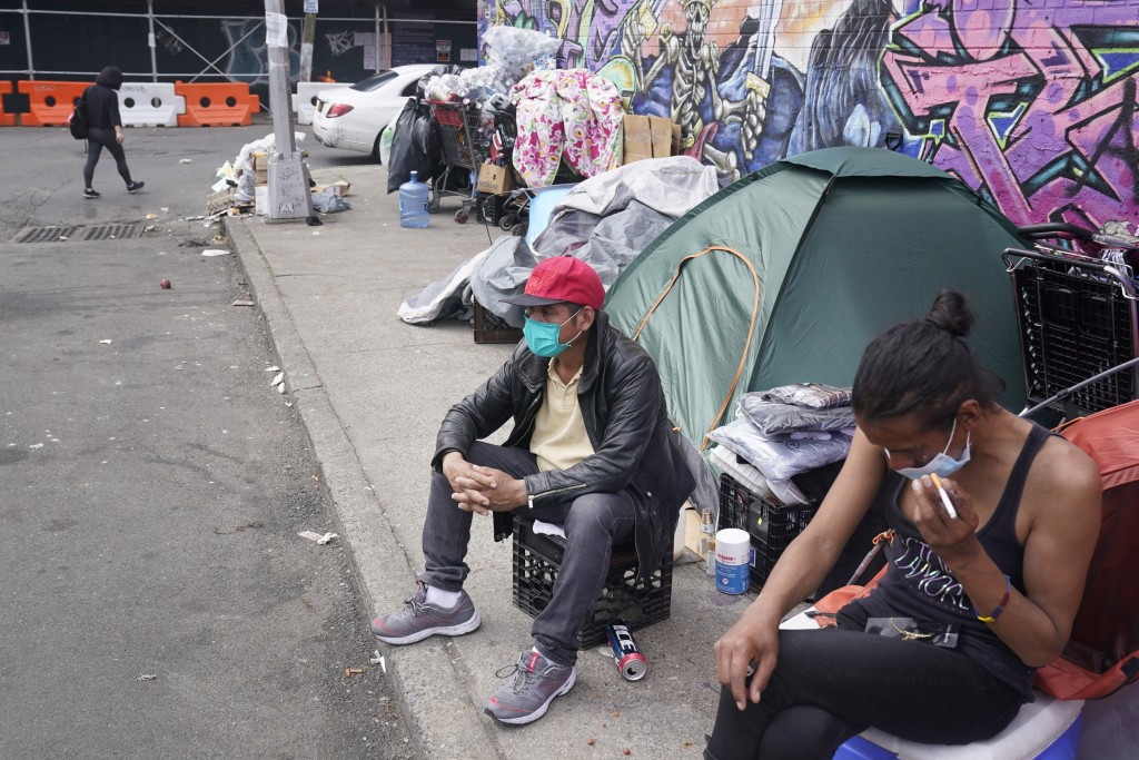 Sotero Cirilo, center, sits on the sidewalk at the homeless encampment where he sleeps in the Queens borough of New York, Wednesday, April 14, 2021. T...