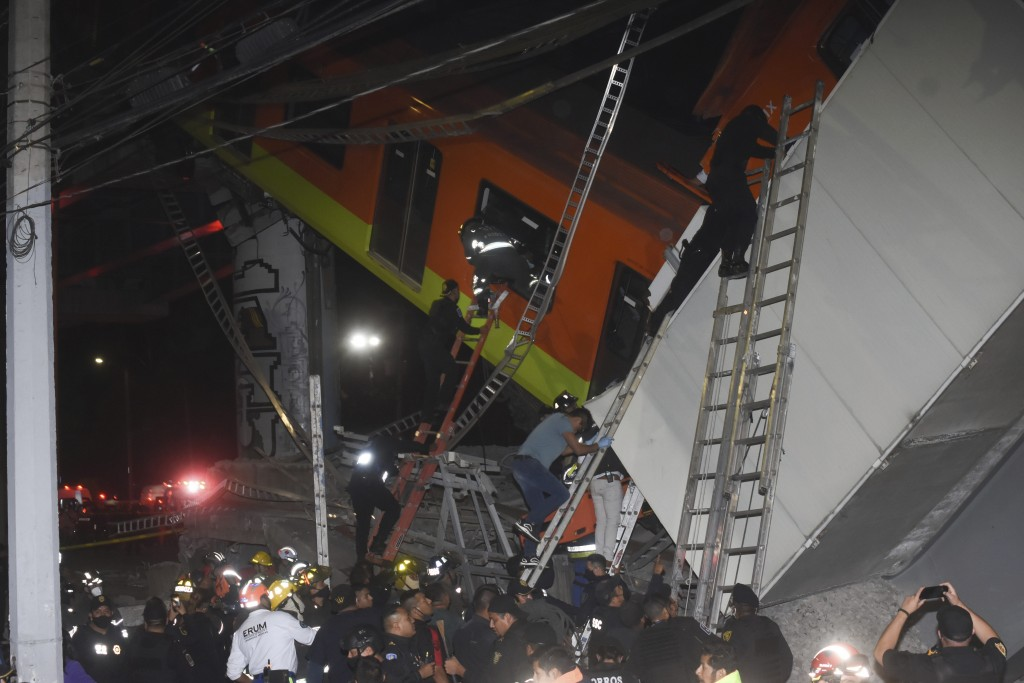 Mexico City fire fighters and rescue personnel work to recover victims from a subway accident after a section of Line 12 of the subway collapsed in Me...