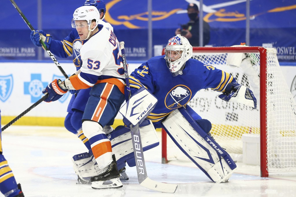 Buffalo Sabres goalie Michael Houser (32) is bumped into by New York Islanders forward Casey Cizikas (53) during the second period of an NHL hockey ga...