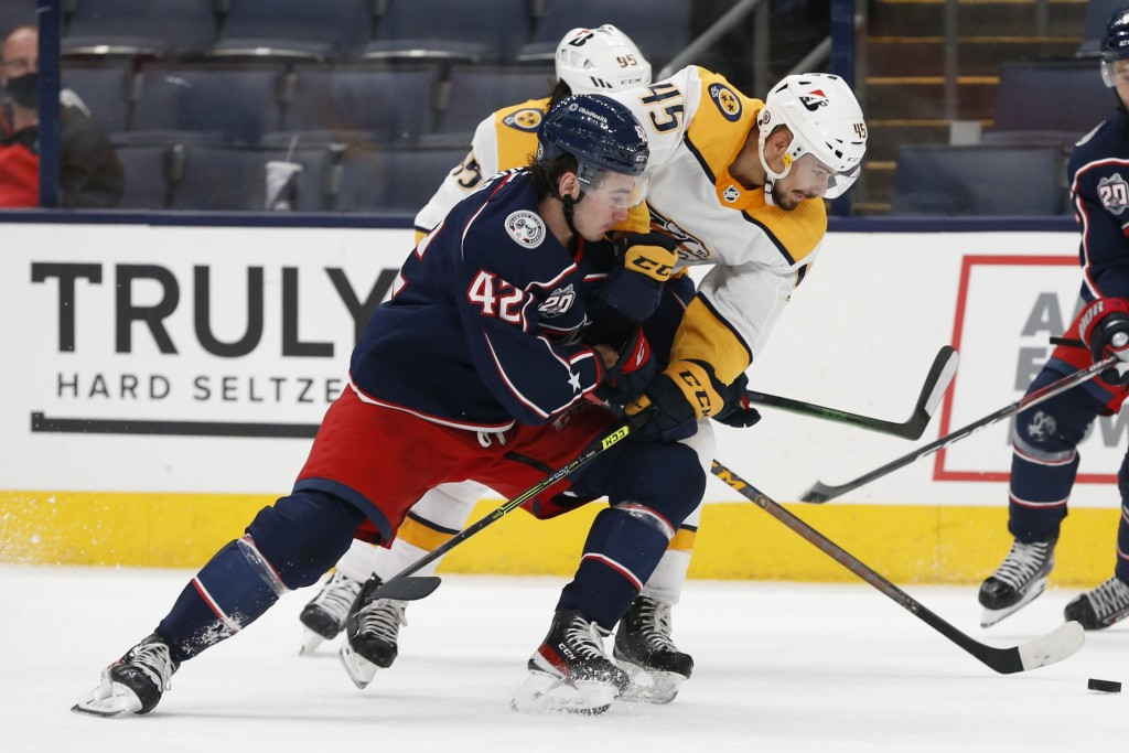 Nashville Predators' Alexandre Carrier, right, and Columbus Blue Jackets' Alexandre Texier fight for the puck during the second period of an NHL hocke...