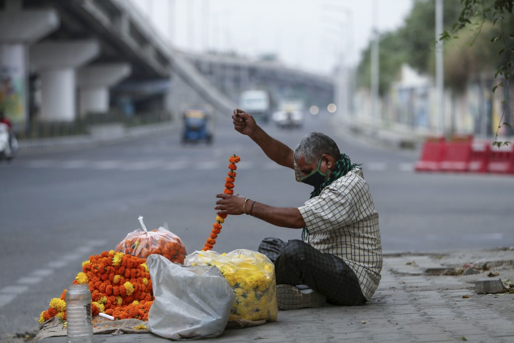 A flower vendor makes garlands by a roadside in Jammu, India, Tuesday, May 4, 2021. COVID-19 infections and deaths are mounting with alarming speed in...