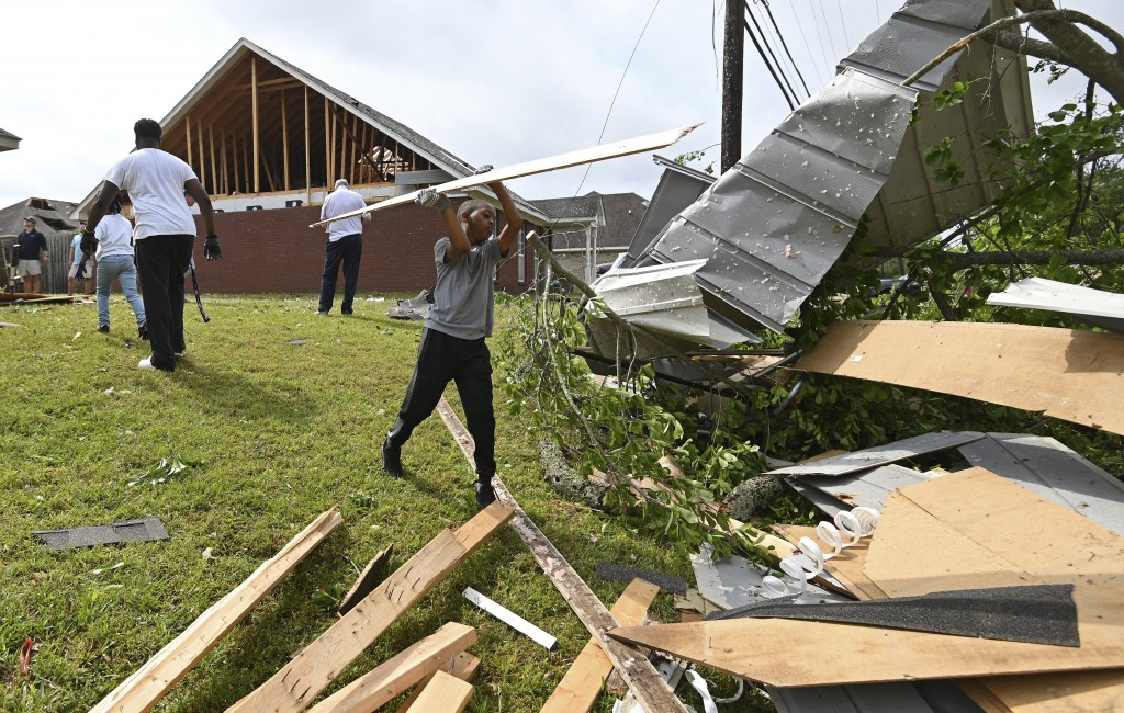 Derrick Pounds Jr. helps his father clean up debris around their house on Elvis Presley Drive in Tupelo, Miss., Monday, May 3, 2021. Multiple tornadoe...