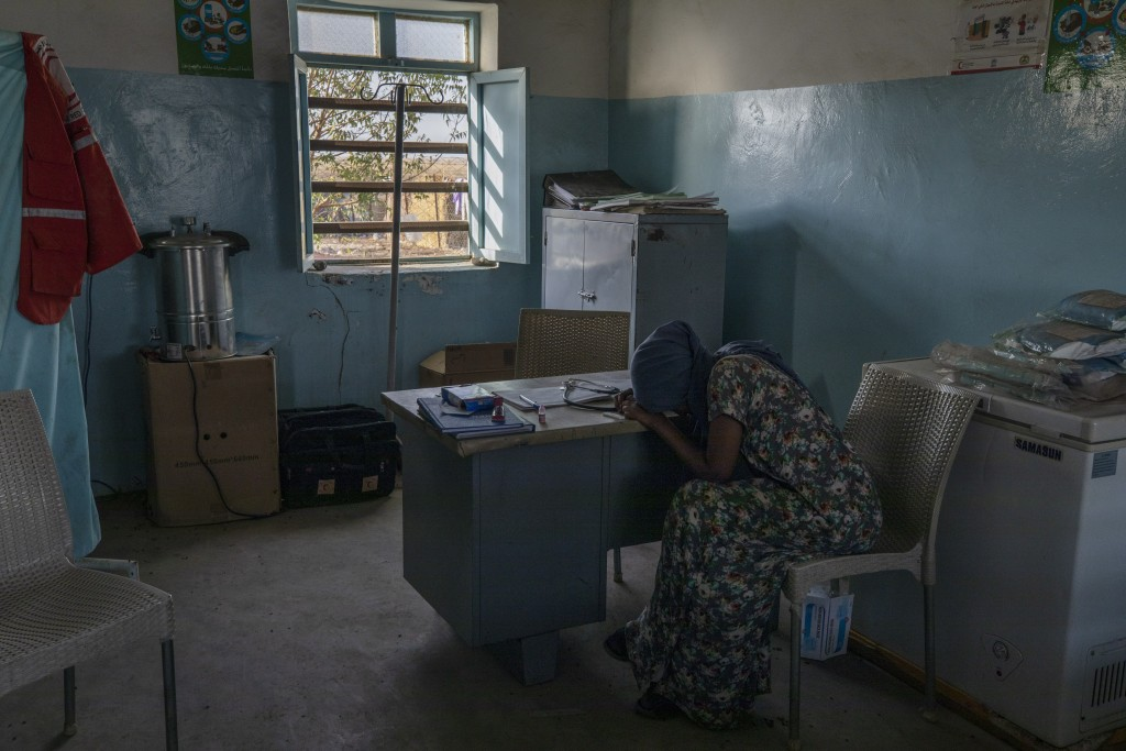 Tigrayan refugee Hareg, 23, from Mekelle, Ethiopia, reacts after learning of her positive malaria test, administered by surgeon and doctor-turned-refu...