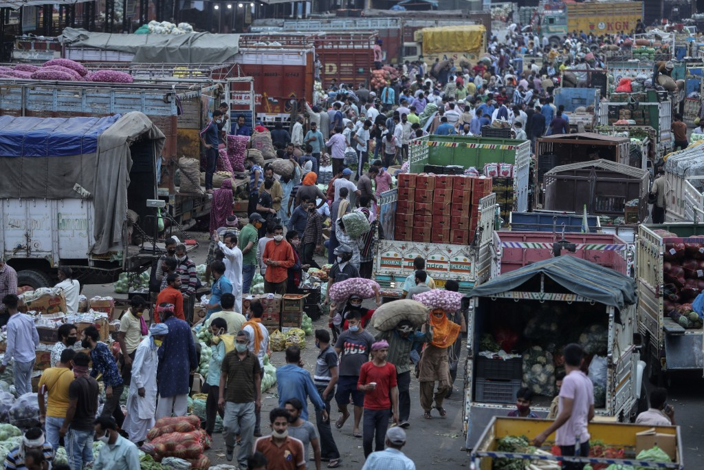 Indians crowd a vegetable market in Jammu, India, Tuesday, May 4, 2021. COVID-19 infections and deaths are mounting with alarming speed in India with ...