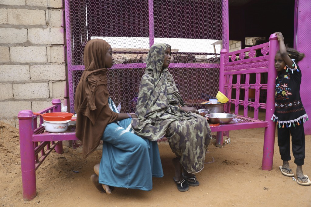 Saadia Ahmed, mother of the Sudanese migrant Mutawakel Ali, sits with her daughters at her home, in Khartoum, Sudan, Friday April 30, 2021. Ali narrow...