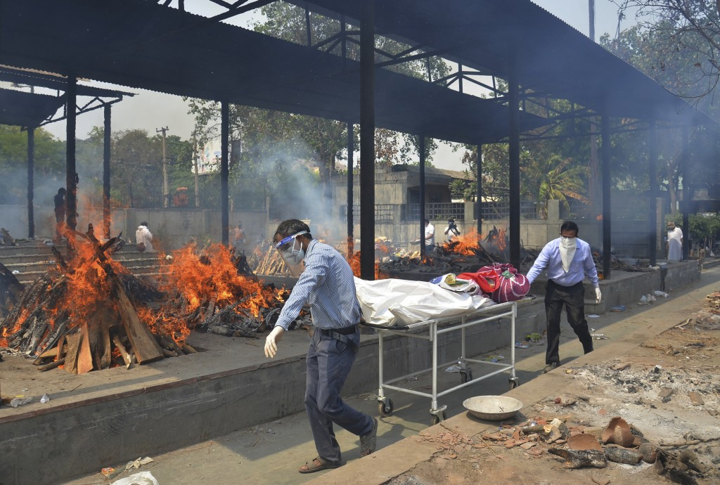 FILE - In this May 1, 2021, file photo, relatives carry the body of a person who died of COVID-19 as multiple pyres of other COVID-19 victims burn at ...