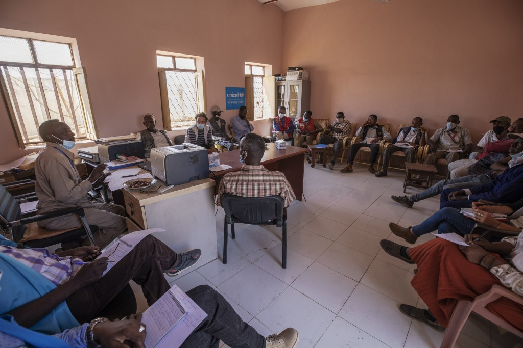 Surgeon and doctor-turned-refugee, Dr. Tewodros Tefera, background center, attends a weekly meeting with all non-governmental organization (NGO) repre...