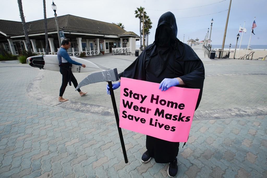 FILE - In this May 8, 2020, file photo, Spencer Kelly, dressed as the grim reaper, demonstrates in favor of the stay-at-home order during the coronavi...
