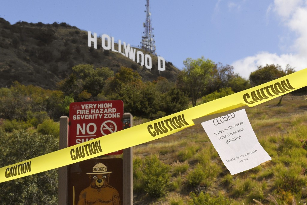 FILE - In this March 28, 2020, file photo, a sign is posted at the closed entrance to Innsdale Trail near the Hollywood sign in Los Angeles, amid the ...