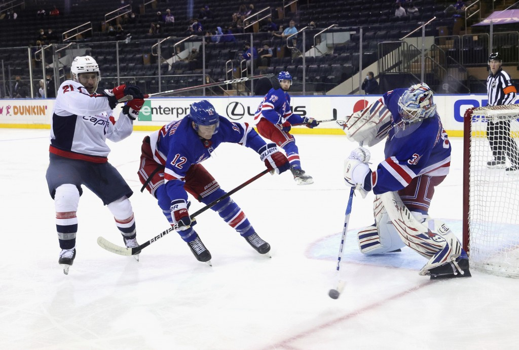 Igor Shesterkin, right, of the New York Rangers, shoots the puck away from Garnet Hathaway, left, of the Washington Capitals during the second period ...