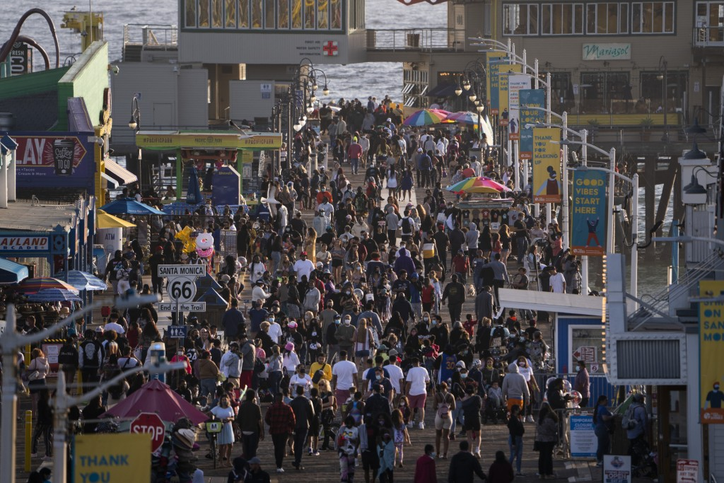 FILE - In this April 7, 2021, file photo, people gather on the Santa Monica Pier in Santa Monica, Calif. Los Angeles County is expected to move Tuesda...
