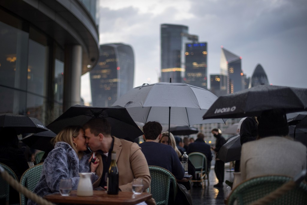 People endure the wet and windy Bank Holiday weekend weather to sit outside a restaurant near Tower Bridge in central London on Monday, May 3, 2021.  ...