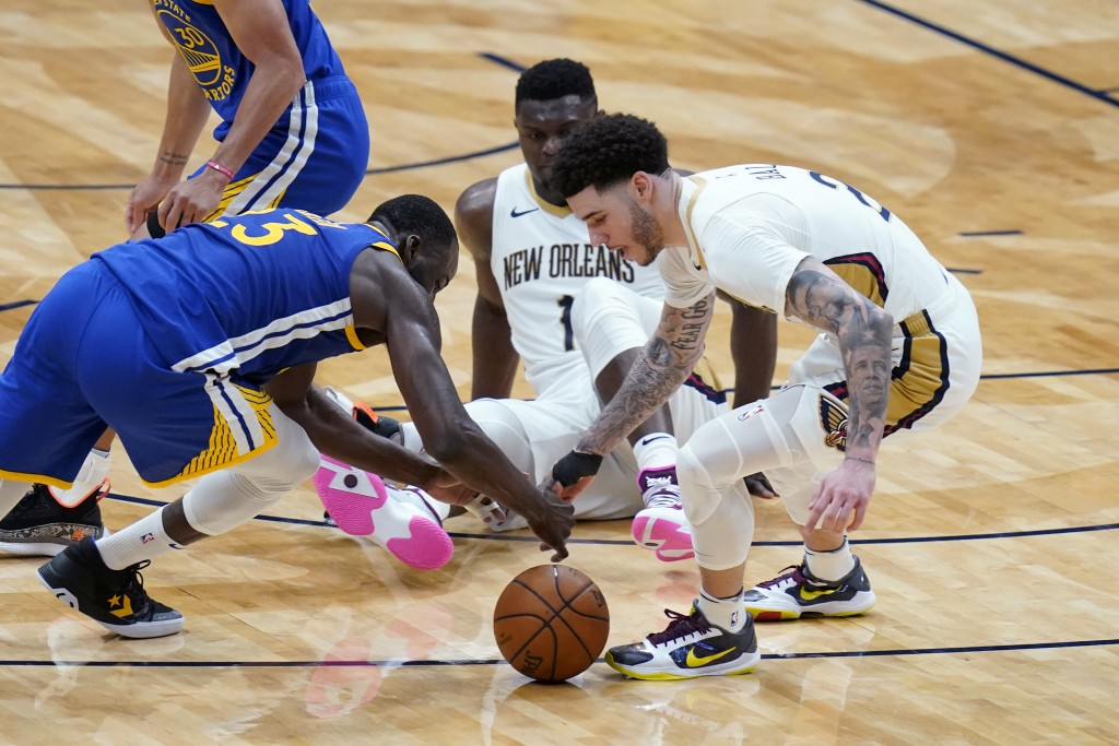 Golden State Warriors forward Draymond Green (23) and New Orleans Pelicans guard Lonzo Ball (2) battle for a loose ball in the second half of an NBA b...