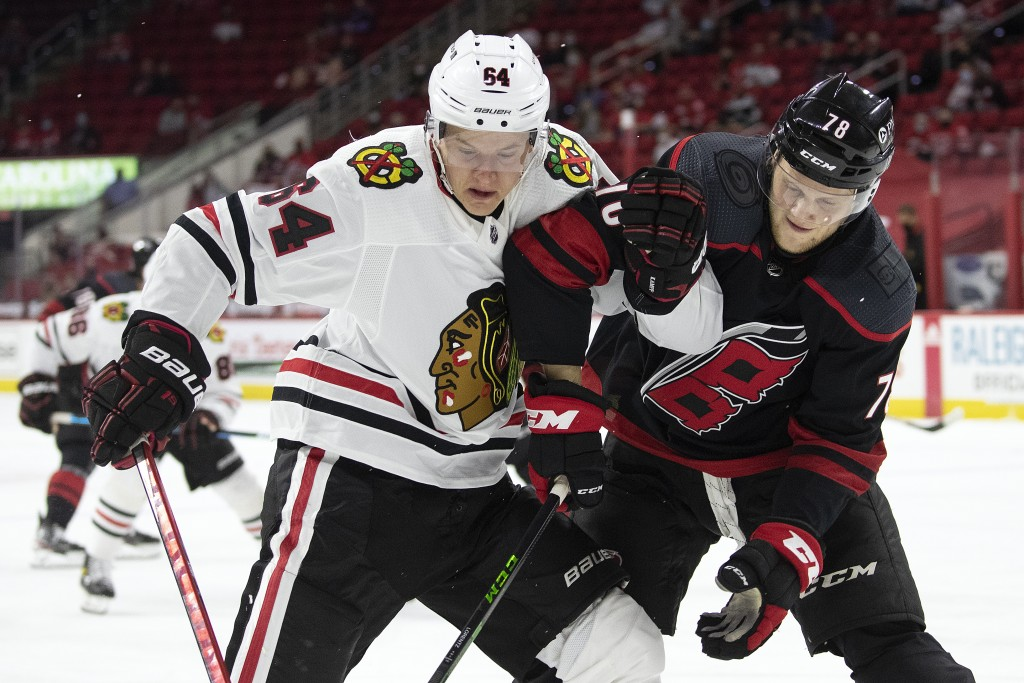 Carolina Hurricanes' Steven Lorentz (78) tangles with Chicago Blackhawks' David Kampf (64) during the first period of an NHL hockey game in Raleigh, N...