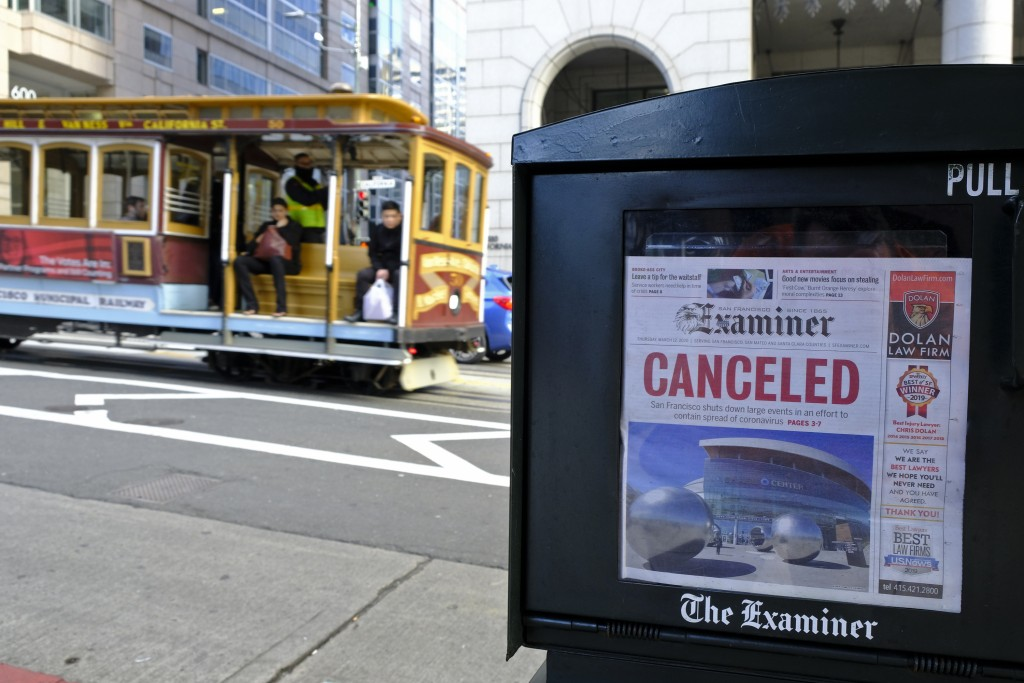 FILE - In this March 13, 2020, file photo, a newspaper headline announcing the closure of large events is displayed as a cable car goes down Californi...