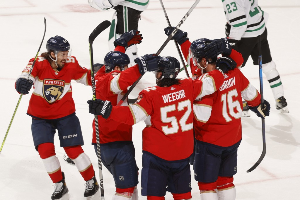 Teammates celebrate the game-winning goal by Florida Panthers center Aleksander Barkov (16) during the overtime period of an NHL hockey game, Monday, ...