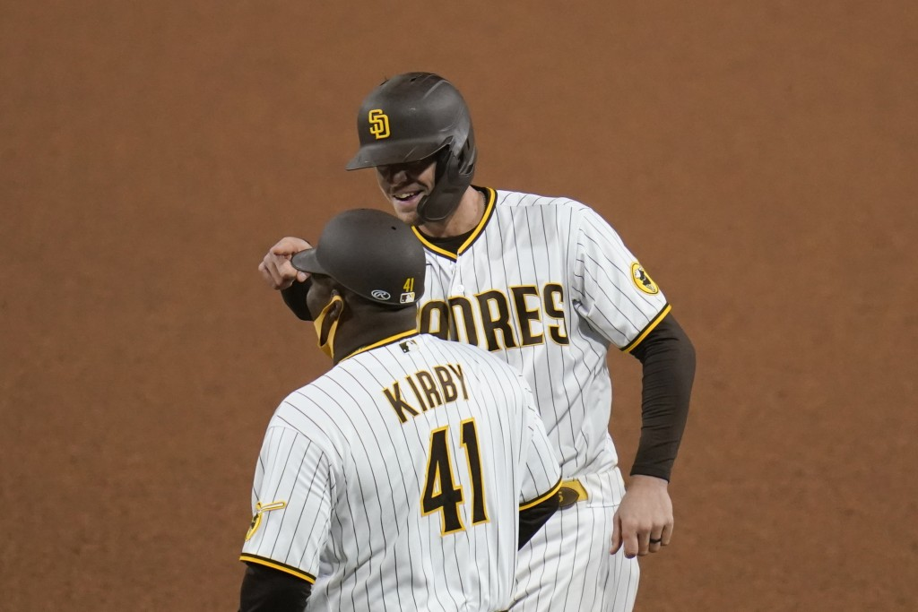 San Diego Padres' Wil Myers, right, reacts after hitting a single as first base coach Wayne Kirby (41) looks on during the seventh inning of a basebal...