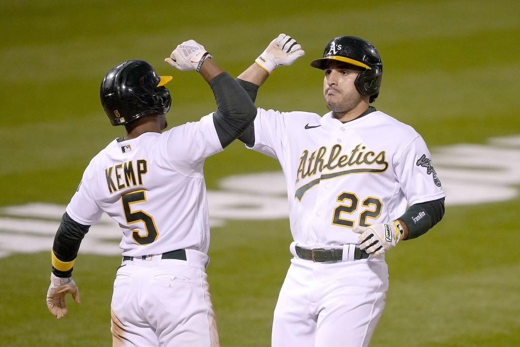 Oakland Athletics' Ramon Laureano (22) gets a forearm-bash with his teammates Tony Kemp (5) after hitting a two-run home run against the Toronto Blue ...