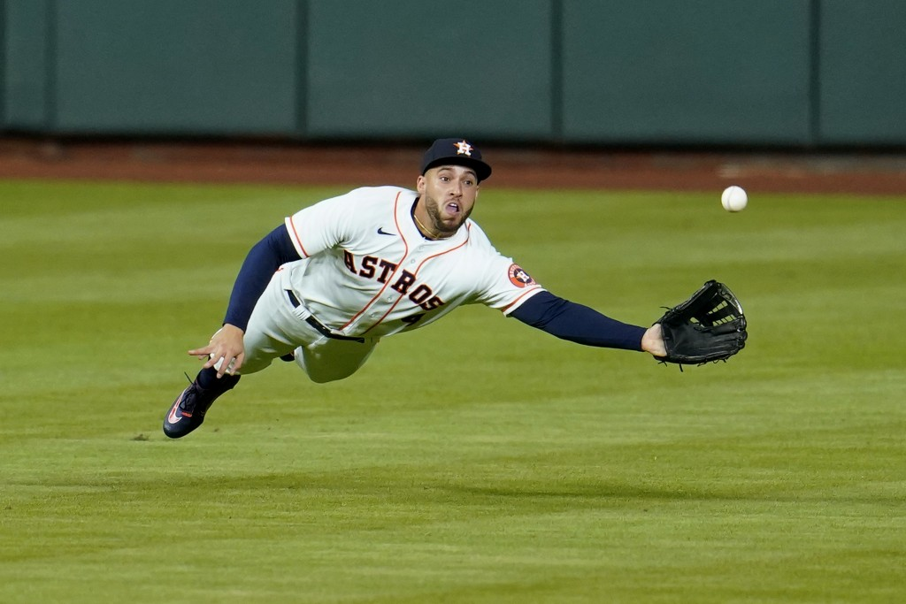 FILE - Inn this July 27, 2020, file photo, Houston Astros center fielder George Springer dives while trying to catch a double by Seattle Mariners' J.P...