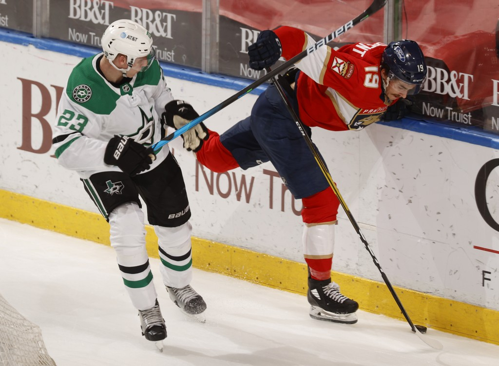 Dallas Stars defenseman Esa Lindell (23) checks Florida Panthers left wing Mason Marchment (19) off the puck during the second period of an NHL hockey...