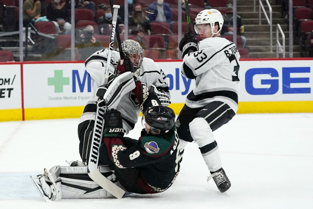 Arizona Coyotes right wing Clayton Keller (9) gets shoved into Los Angeles Kings goaltender Jonathan Quick, left, by Kings defenseman Tobias Bjornfot ...